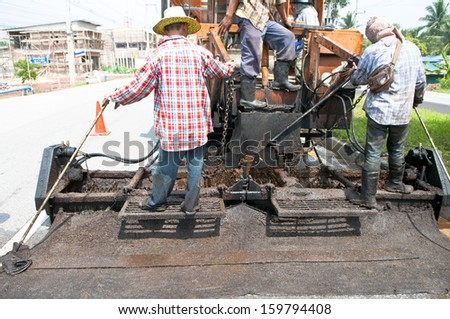 Close up on workers operation paving road renovation by Asphalt Para Slurry Seal truck - stock photo