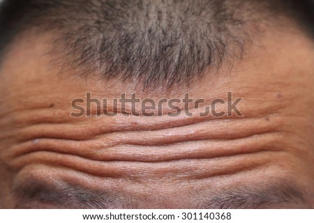 close-up on wrinkled forehead - stock photo