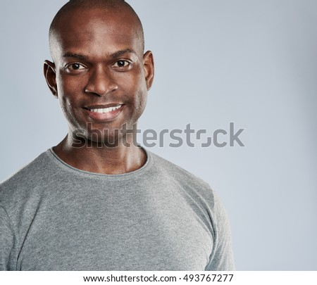 Close up on young attractive grinning Black man with shaved head in gray workout shirt over background with copy space