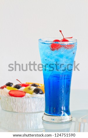 Close up one blue cocktail and cherry in glass and fresh fruited cake - stock photo