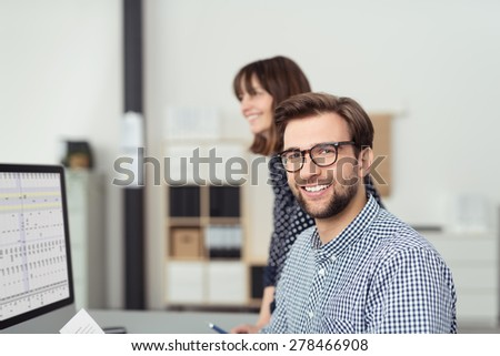 Close up Optimistic Young Bearded Businessman with Eyeglasses Sitting at his Worktable and Smiling at the Camera with his Female Co-worker Behind Him. - stock photo