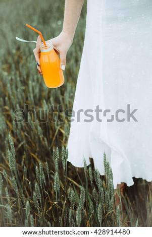 Close up orange juice. Woman drinking orange juice outdoor. - stock photo