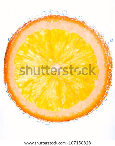 close-up orange slice in clear water with bubbles - stock photo