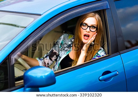 Close up outdoor lifestyle travel photo of young blonde hipster student woman driving car, glasses and bright clothes, surprised emotions, angry and sad about traffics . - stock photo
