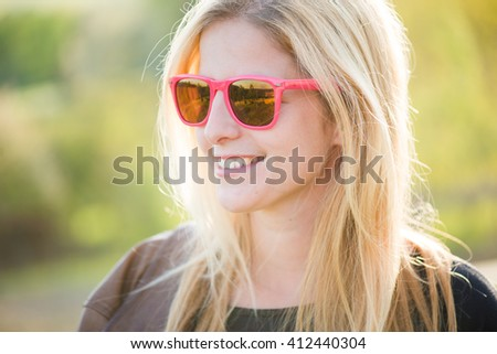 Close up outdoor portrait. Blonde woman posing outdoor in pink sunglasses. - stock photo