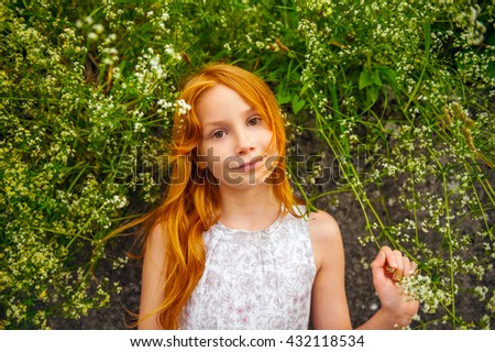 Close up outdoor portrait of adorable little girl of 8-9 years old . Red hair sweet young girl of 7-8 years old. - stock photo