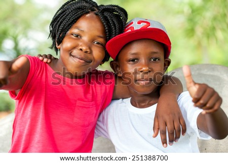 Close up outdoor portrait of African brother and sister doing thumbs up.