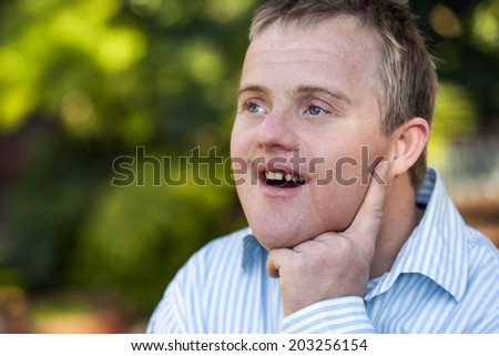 Close up outdoor portrait of cute handicapped boy looking aside with wondering face expression. - stock photo