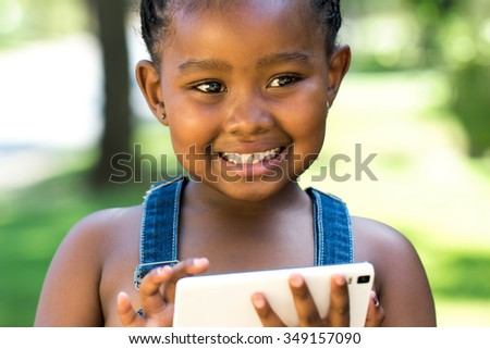 Close up outdoor portrait of cute little african girl playing on digital tablet. - stock photo