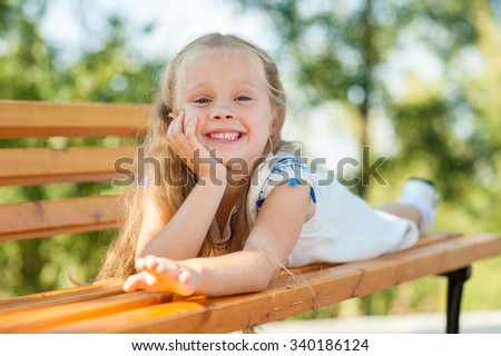 Close-up outdoor portrait of little girl lying on bench in a park, leisure in the nature.  - stock photo