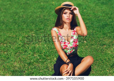 Close up outdoor portrait of seductive young  woman  smiling , sitting on green  fresh grass in sunny spring park . Wearing stylish straw hat ,  colorful  crop top and black skirt. Perfect tan skin.  - stock photo