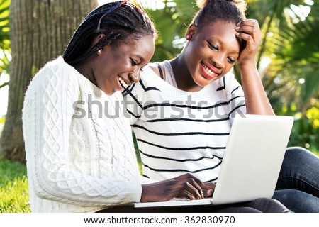 Close up outdoor portrait of two afro american teen girls socializing on laptop in park.