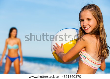 Close up outdoor portrait of young preteen holding inflatable plastic beach ball with mother in background. - stock photo