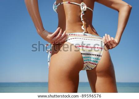 close up outdoor shot of young woman in white bikini, sunbathing at sea shore - stock photo