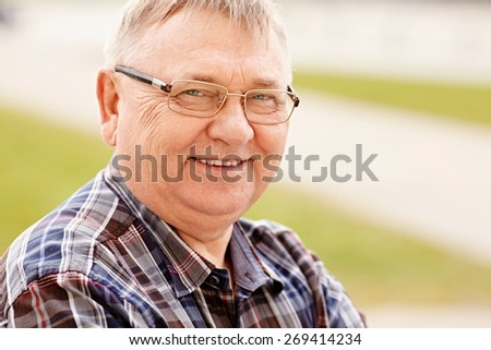 Close up outdoors portrait of smiling middle aged man in glasses and cheered shirt - stock photo
