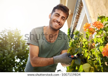Close up outdoors portrait of young cheerful bearded man in blue t-shirt smiling in camera, working in garden with tools, cutting leaves, watering flowers