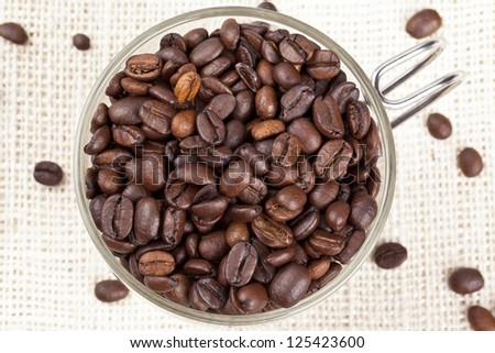 Close-up overhead shot of a pile coffee beans in coffee mug. - stock photo