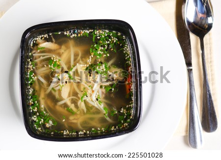 Close up overhead view of a bowl of tasty chicken noodle soup with herbs in a minestrone broth served at table - stock photo