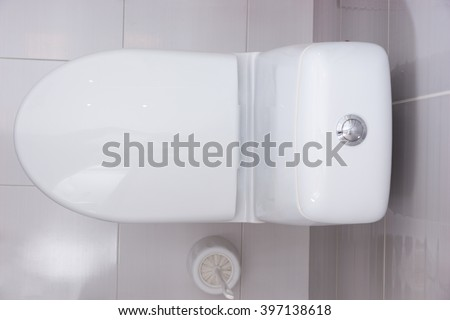 Close up overhead view of a plain white toilet with the seat shut and a toilet brush for cleaning alongside in a grey and white tiled bathroom - stock photo
