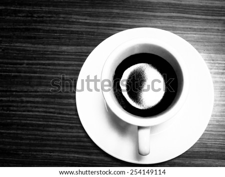 Close up overhead view of cup of coffee on a wooden table . B&W photo. Selective focus. - stock photo