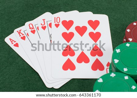 Close up overhead view of playing cards on table beside three stacks of poker chips