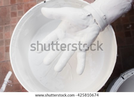 Close up Painter mixing white, hand with colors mix, painted home in the work : ancient form paint mixing : (select focus front hand and soft-focus background) - stock photo