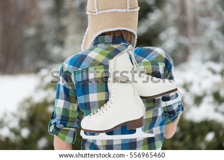 Close up pair of White Ice Skates, woman holding vintage ice skates outdoor. Winter sport concept.