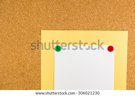 Close up paper on cork board with sticky note pinned