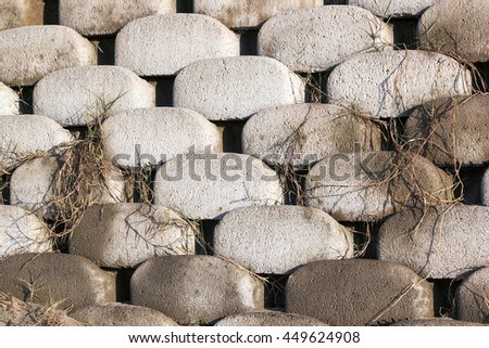 Close up patterns and textures of curved interlocking concrete retaining wall bricks with dry vegetation growth creeping through - stock photo