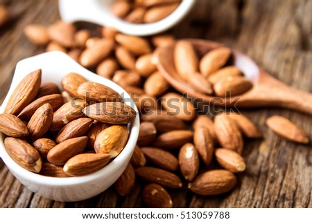 close up Peeled almonds nut  in small white cup on wooden  background