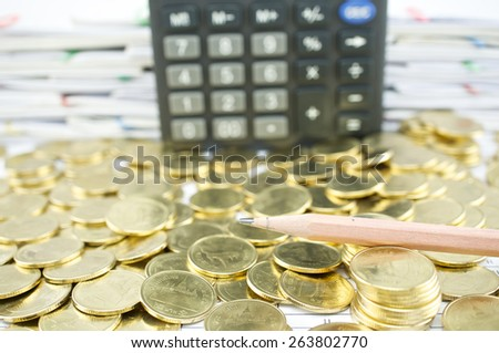 Close up pencil on heap of gold coins with calculator and pile of paperwork as background. - stock photo