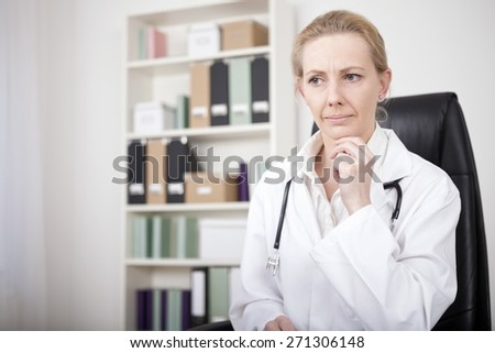 Close up Pensive Adult Female Doctor Sitting at her Office and Looking Afar with One Hand on her Chin - stock photo