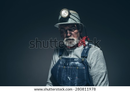 Close up Pensive Bearded Old Gold Miner, Looking Into Distance Seriously Against Gray Gradient Background - stock photo