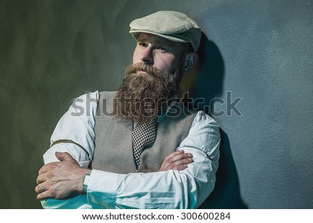 Close up Pensive Middle Aged Bearded Man with Flat Hat Leaning Against Wall with Arms Crossed and Looking Into the Distance. - stock photo