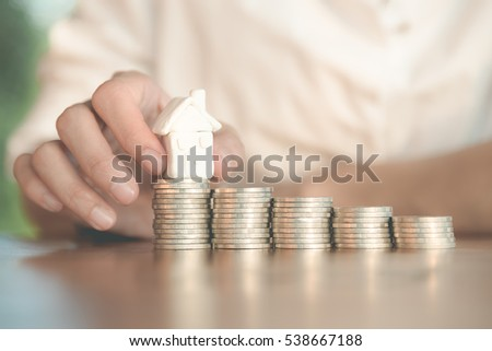 Close up pf the people hand putting the house on the row of coins in saving for buying house