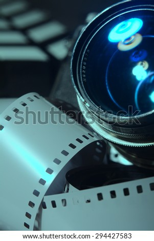 Close-up photo movie camera lens. Roll film cinema in the foreground. Movie clapper in the background as blurring
