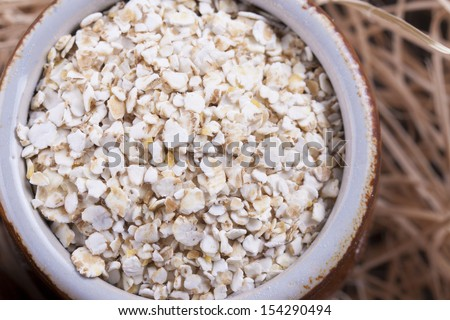 Close up photo of a cereal grain product in a clay cup - light brown barley flakes placed on a wooden shavings.