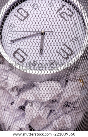 Close-up photo of a clock in refuse bin with other office rubbish like document and papers, concept of time management at work - stock photo