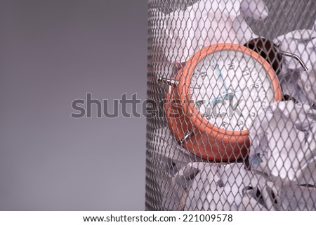 Close-up photo of a clock in refuse bin with other office rubbish like documents and papers, concept of time management at work, isolated on grey background with copy place - stock photo
