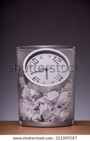 Close-up photo of a clock in refuse bin with other office rubbish standing on the table in office isolated on grey background with copy place, concept of time management at work