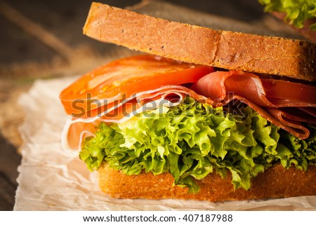 Close-up photo of a club sandwich. Sandwich with meet, prosciutto, salami, salad, vegetables, lettuce, tomato, onion and mustard on a fresh sliced rye bread on wooden background. Olives background. - stock photo