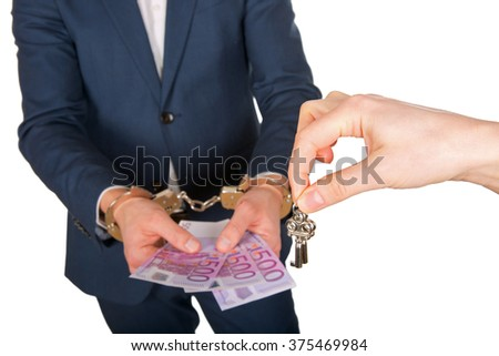 Close up photo of a handcuffed businessman hands holding euro bank notes - stock photo
