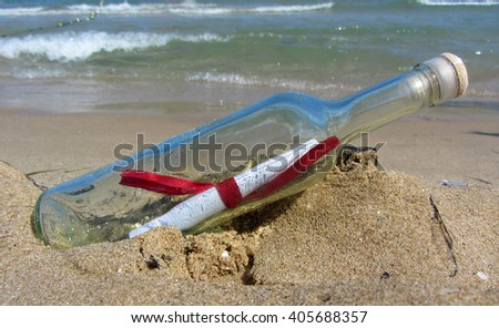 Close up photo of a message in a bottle in beach sand.