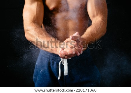 Close-up photo of a muscular torso and hands