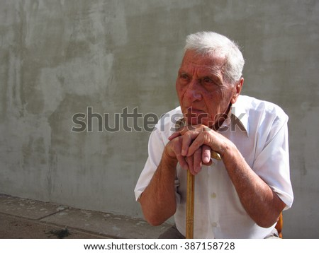 Close up photo of a retired old man in his eighties, leanin on his cane and thinking about the future and the past. - stock photo
