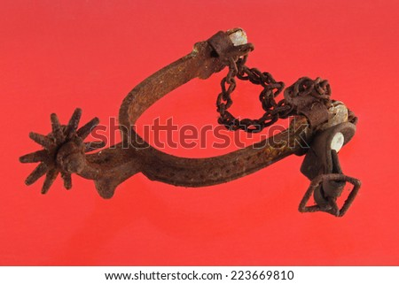 Close up photo of a riding spur on red background. - stock photo