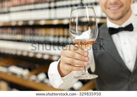 Close up photo of a sommelier stretching his hand holding a glass of white wine, standing smiling in a store during a degustation, selective focus