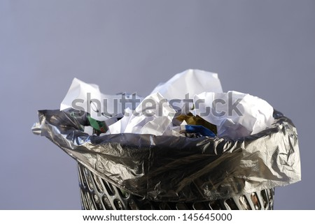 Close up photo of a trash can full of papers - stock photo