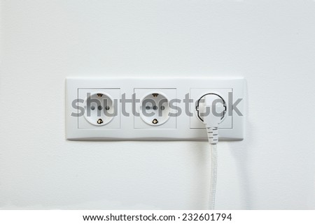 Close up photo of a white power plug plugged in a triple electric socket  - stock photo