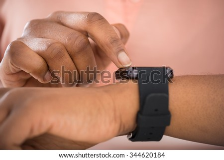 Close-up Photo Of African Person Using Smartwatch - stock photo